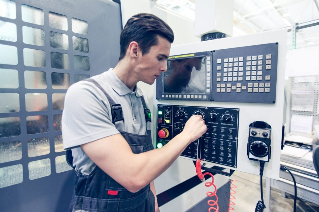 Worker pressing programming buttons on CNC machine control board in factory