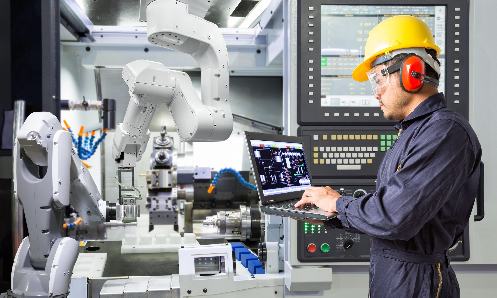 Engineer using laptop computer for maintenance automatic robotic arm with CNC machine in smart factory.