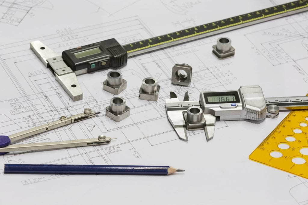 Digital calipers, protractor, lead pencil, small machined parts laying on engineering drawing