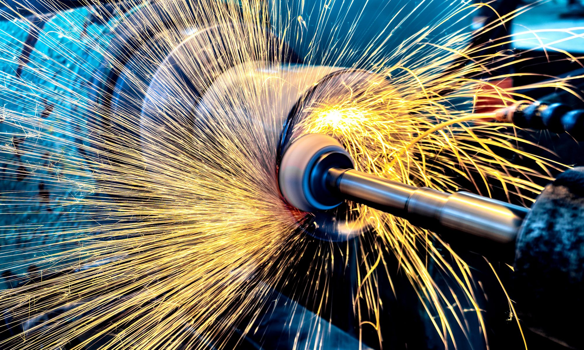 High abrasive grinder machining a cylinder and throwing sparks
