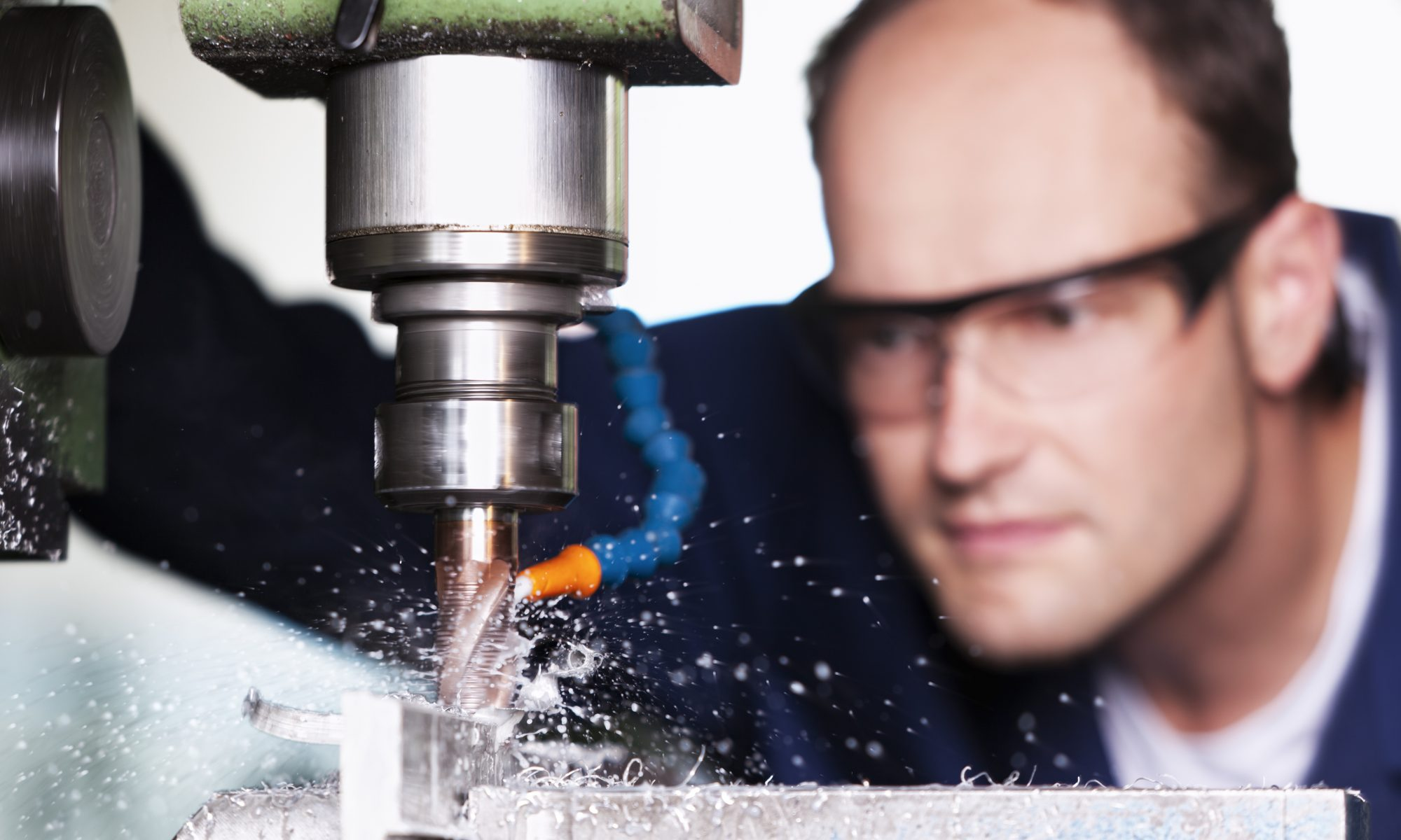 Man wearing safety glasses closely watching milling machine drilling into a block of metal