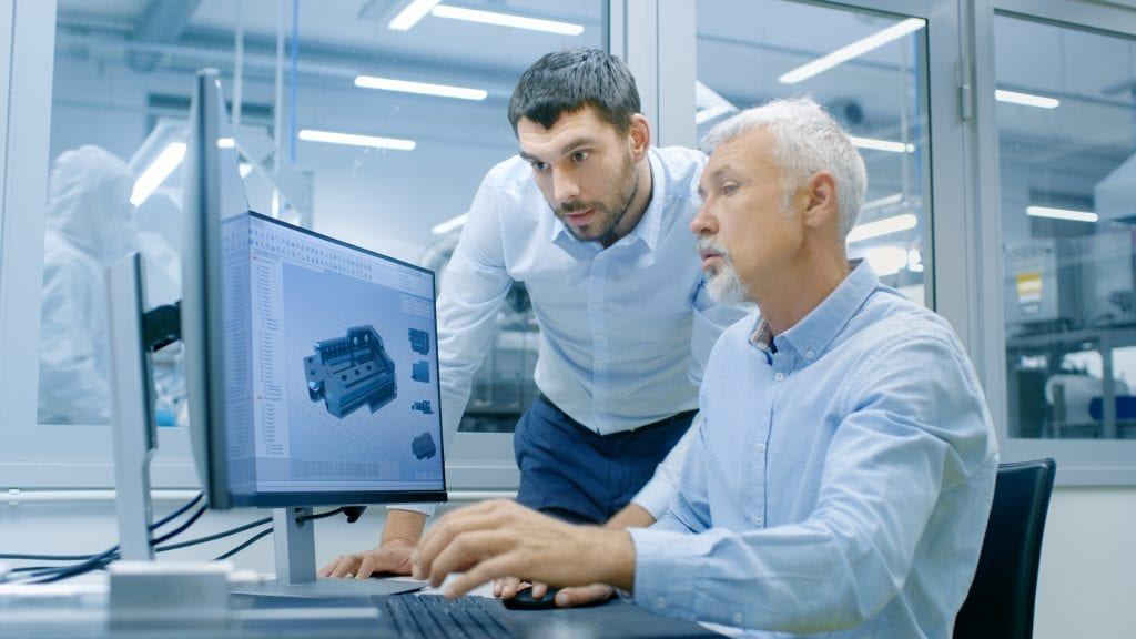Older gentleman sitting, looking at a 3D model on a computer screen with younger man leaning over to see