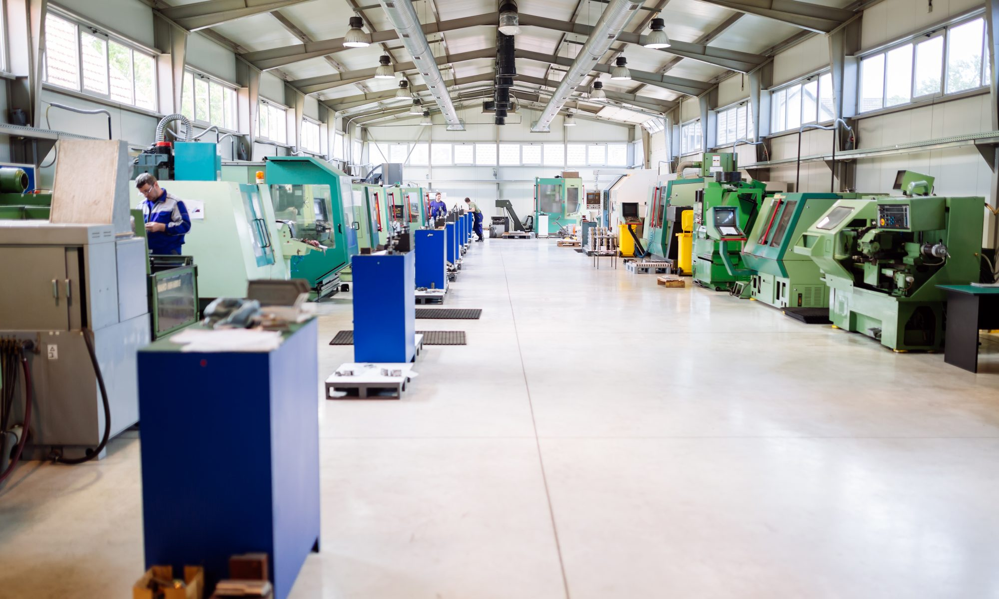 Looking down a factory aisle lined with CNC machines on both sides